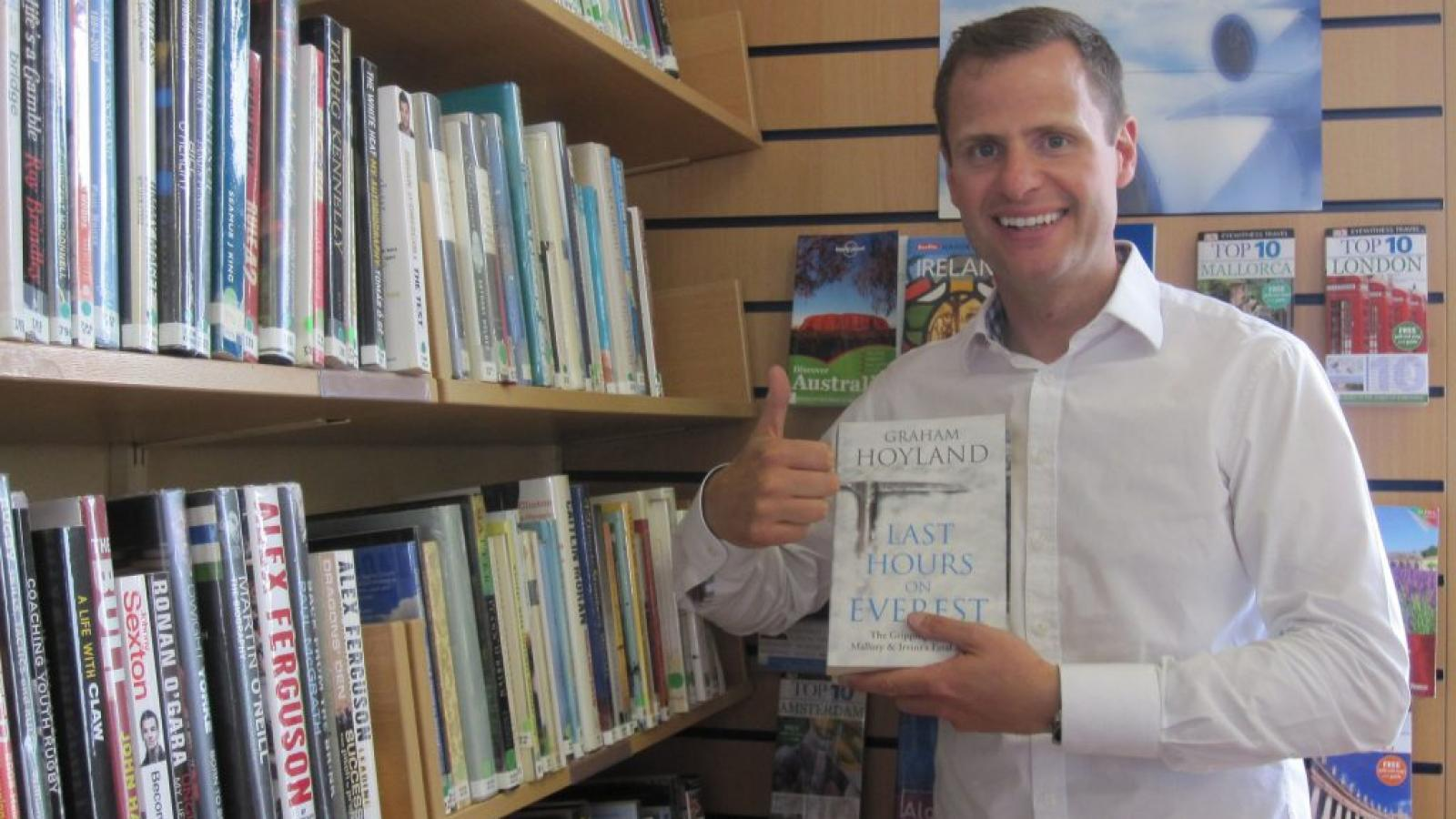 John Burke holding a copy of his book